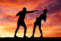 silhouettes-two-fighters-sunset-background-31912699